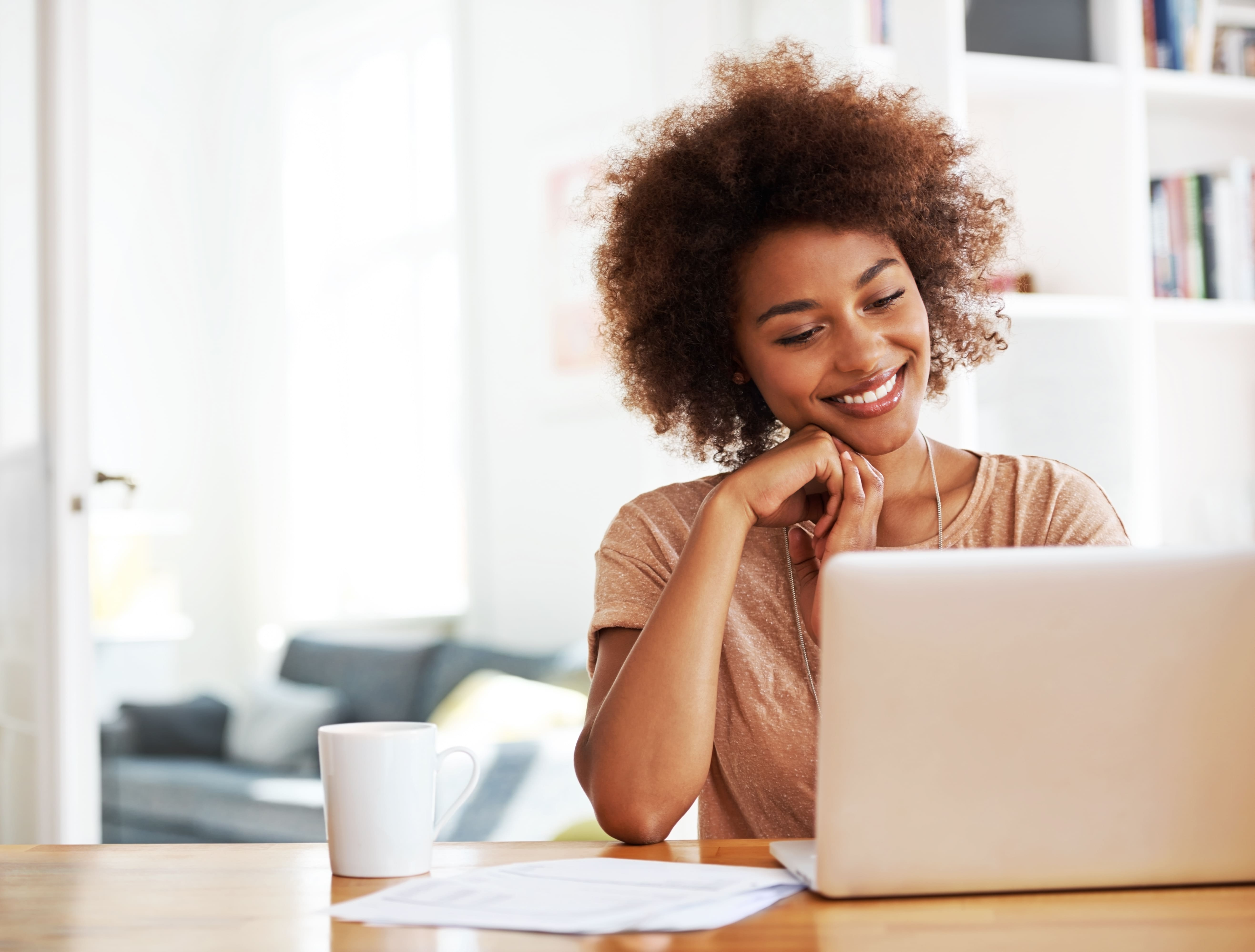 woman smiling as she works in her home office