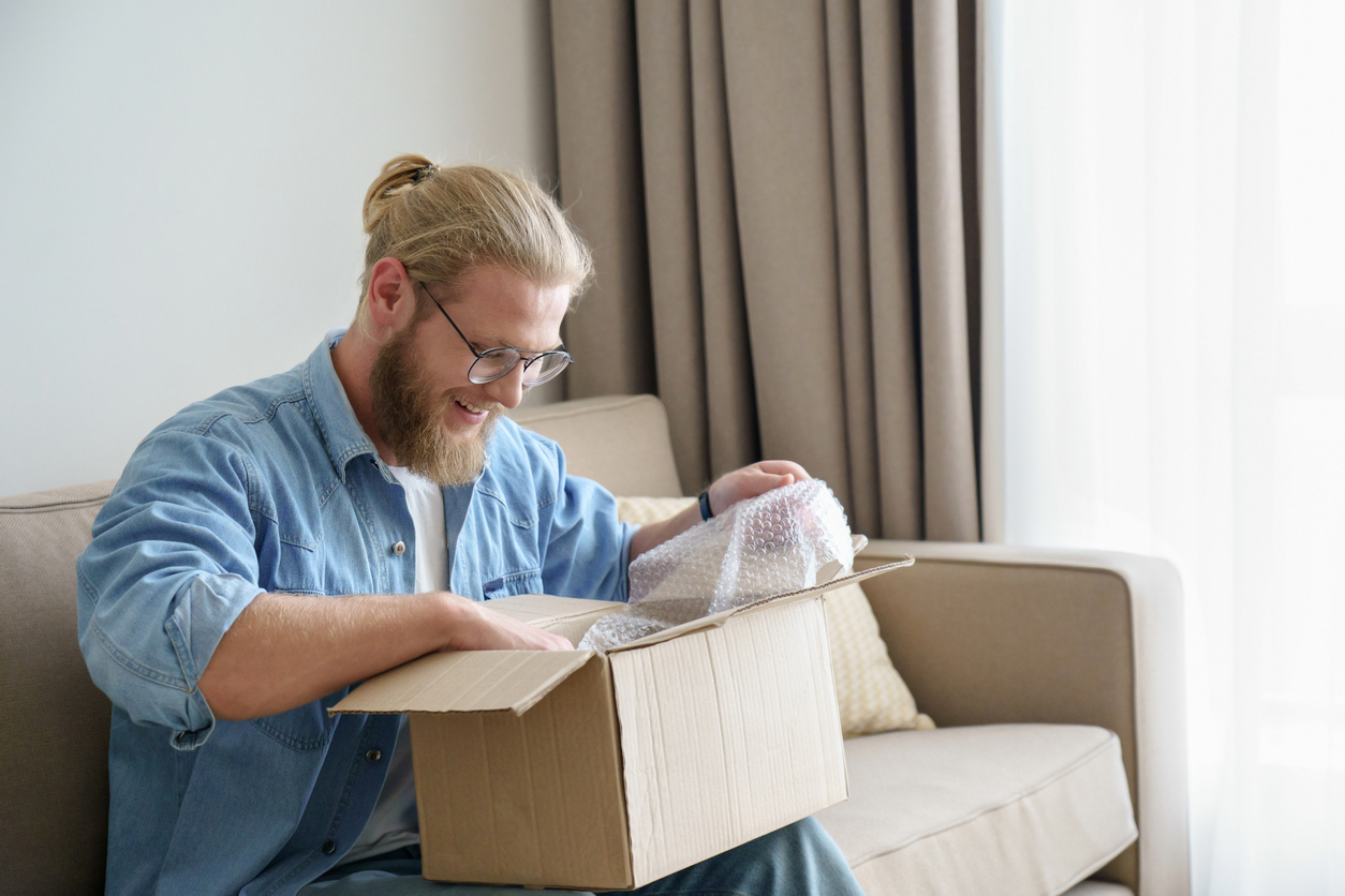 man happily opening a delivered package