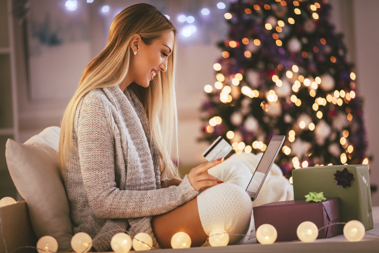 Happy young woman relaxing at home and online buying Christmas presents on laptop.