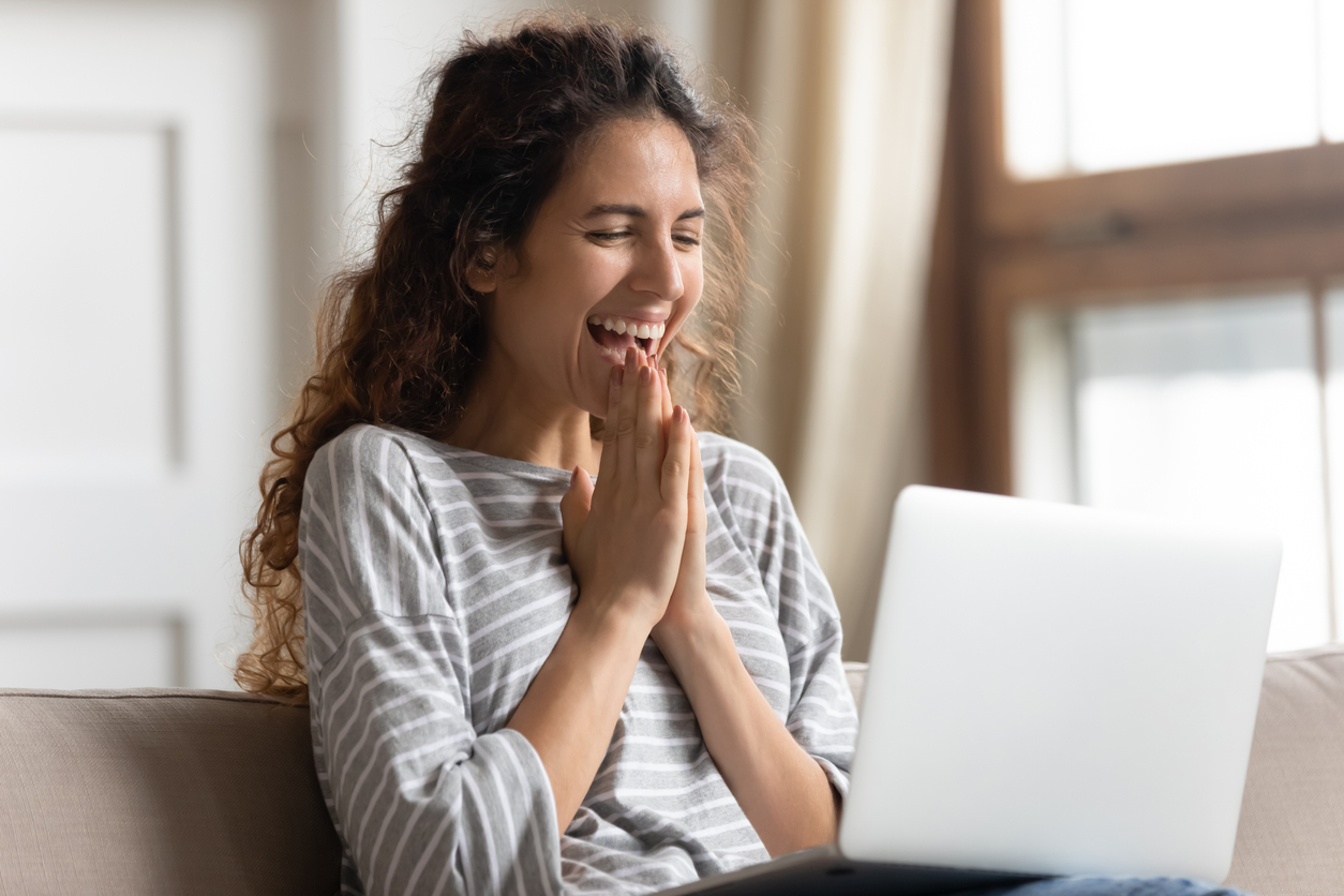 Dropshipper looking happily at her laptop